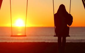 Back view portrait of a single woman silhouette sitting on a swing contemplating sunset