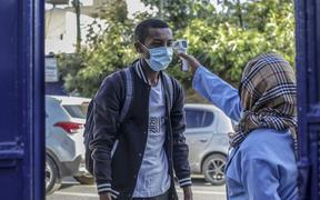 A student has his temperature measured before entering school in Addis Ababa, Ethiopia, on 26 October Schools reopened following a seven-month closure as part of government restrictions to stem the spread of Covid-19.