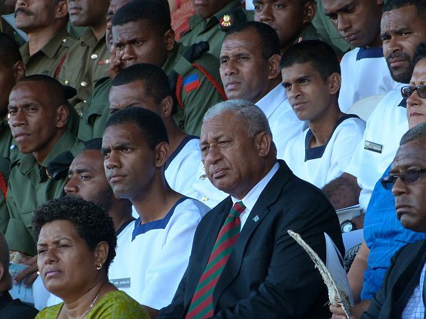 Fiji's Prime Minister, Frank Bainimarama, sitts among soliders at thanksgiving service for release of UN peacekeepers.