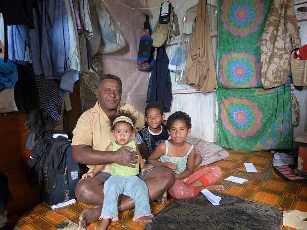 Tevita and young grandchildren in a room with a couple of mattresses on floor and clothes hanging on walls in their home in a squatter settlement in Suva