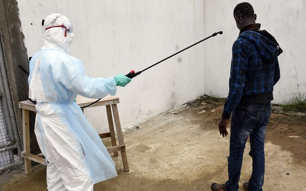 A man is decontaminated by a health worker at a hospital in the Liberian capital Monrovia.