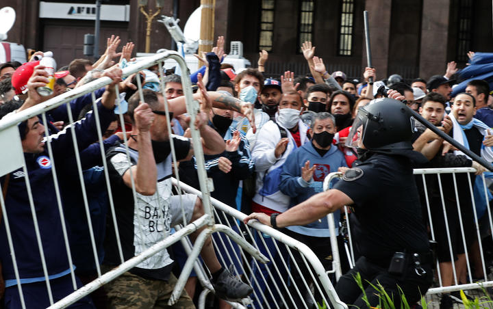 Diego Maradona's fans clash with police as they try to get in to Government House to pay tribute to late football legend Diego Maradona, in Buenos Aires, 26 November.