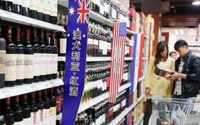 --FILE--Chinese customers shop for wine imported from Australia, the United States or France at a supermarket in Xuchang city, central China's Henan province, 17 October 2013.