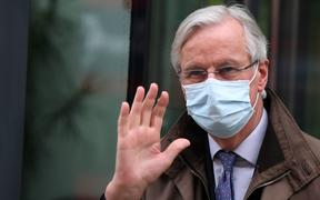 EU chief negotiator Michel Barnier wearing a protective face covering to combat the spread of the coronavirus, waves to members of the media as he leaves a conference centre as negotiations on a trade deal between the EU and the UK continue in London on November 28, 2020.