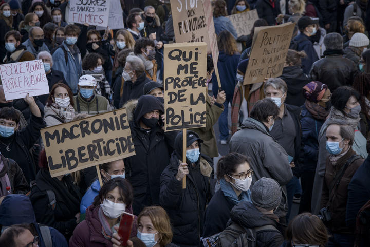 Protesters in Paris hold signs criticising the Global Security Law, and French president Emmanuel Macron.