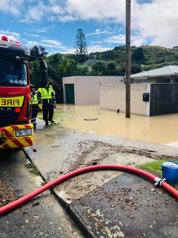 Fire fighters trying to pump water from a Plimmerton home.