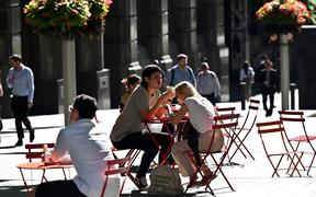 People spend their lunch hour in the central business district of Sydney on November 3, 2020. (Photo by Saeed KHAN / AFP)