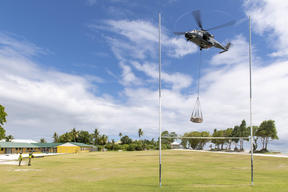 Air crew on a RNZAF NH90 helicopter deliver an underslung load of equipment. A specialist team from NZ Army's 5 Movements Company offloaded equipment in landing zones on the atolls.