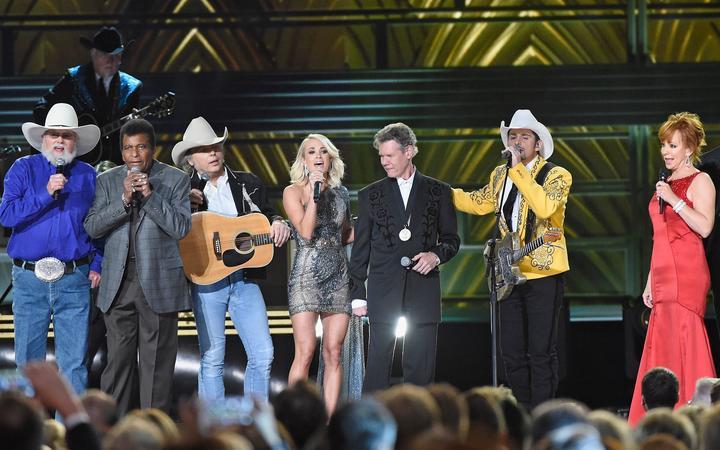 NASHVILLE, TN - NOVEMBER 02: (L-R) Charlie Daniels, Charley Pride, Dwight Yoakam, Carrie Underwood, Randy Travis, Brad Paisley, Reba McEntire,  perform onstage at the 50th annual CMA Awards at the Bridgestone Arena on November 2, 2016 in Nashville, Tennessee.