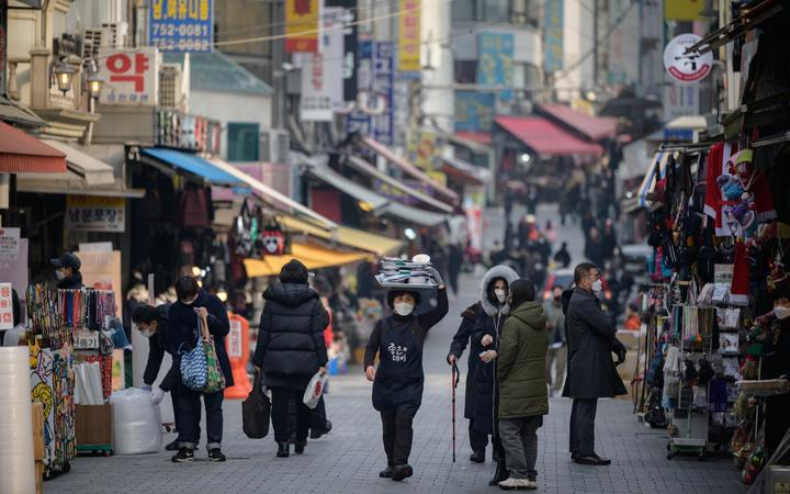 A restaurant worker carries a tray of food through Namdaemun market in Seoul on 11 December 2020.
