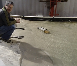 Crile Doscher with the 1:50 scale model of Wairewa/Lake Forsyth. He is crouching on Kaitorete Spit, the outlook to the lake is to his left, and the bricks are simulating breakwaters.