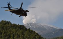 A military helicopter leaves a temporary landing site for a rescue mission on Japan's Mount Ontake.