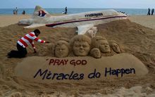 Indian sand artist Sudersan Pattnaik gives final touches to a sand sculpture with a message of prayers for missing Malaysian Airlines flight MH370.