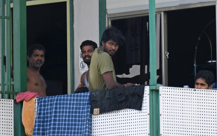 Men look out from a dormitory used by foreign workers at Cochrane Lodge 2, which has been made an isolation area to prevent the spread of the COVID-19 coronavirus, in Singapore on April 15, 2020.