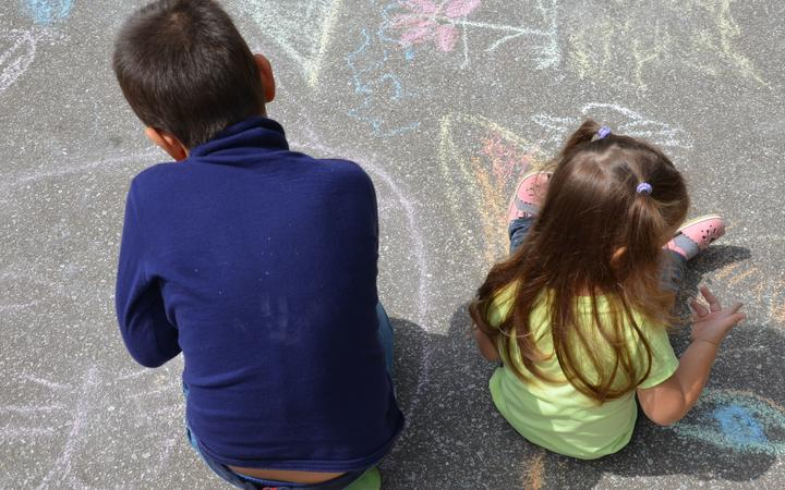 Boy and girl drawing with chalk home orphan child dream. children paint on the pavement. happy childhood on the street. isolation out.