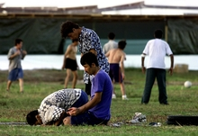 A small group of Muslim refugees pray at sunset while other refugees (background) participate in a football match at a camp for the asylum seekers on the small island of Nauru, 20 September 2001.