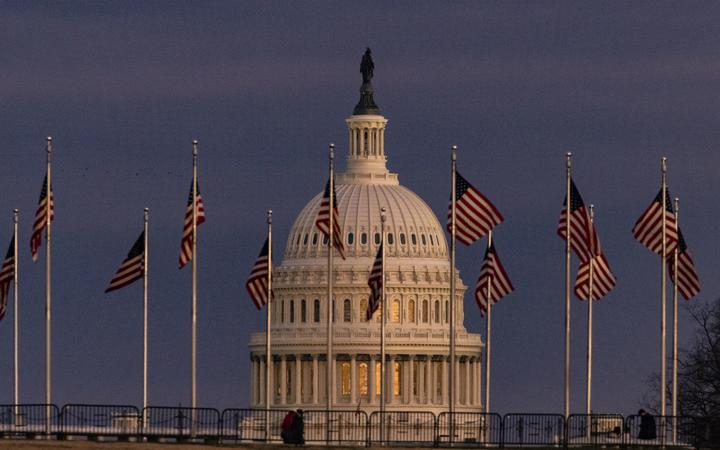 WASHINGTON, DC - DECEMBER 26: The US Capitol Building is seen past the Washington Monument as the sun sets on December 26, 2020 in Washington, DC.