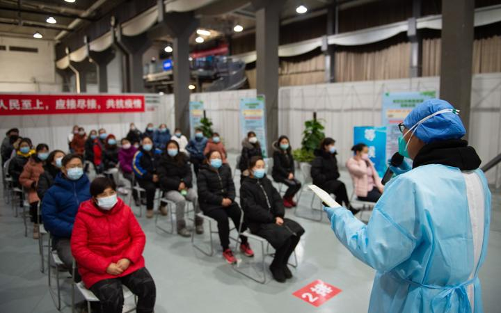 People listen as a staff member elaborates precautions before receiving Covid-19 vaccine shots at an inoculation site in Chaoyang District, Beijing, capital of China, Jan. 5, 2021.