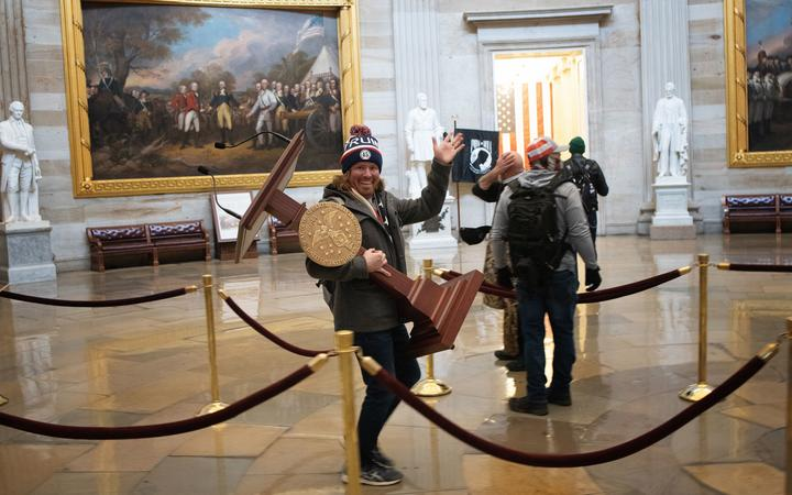 A pro-Trump protester carries the lectern of US Speaker of the House Nancy Pelosi through the Rotunda of the US Capitol Building after a pro-Trump mob stormed the building on January 06, 2021 in Washington, DC.