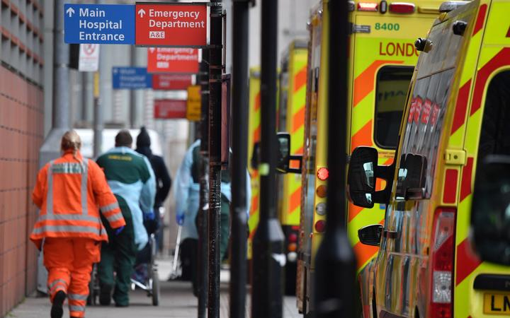 Paramedics unload a patient from an ambulance outside the Royal London Hospital in east London on January 8, 2021.