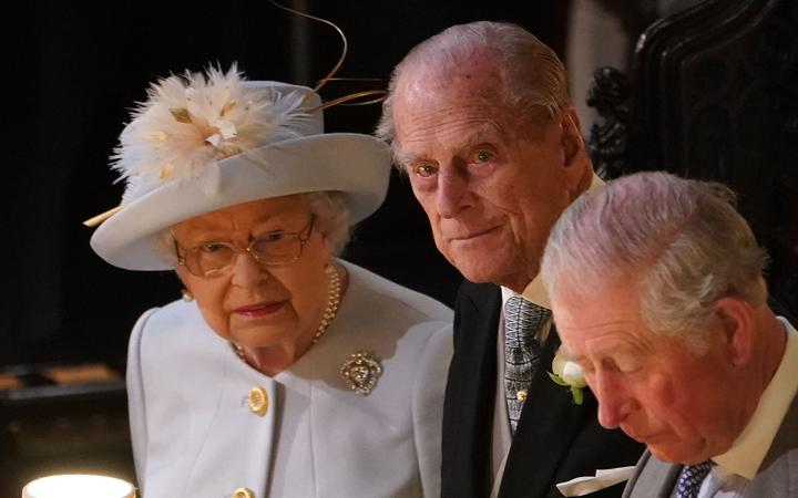 Britain's Queen Elizabeth II (L), Britain's Prince Philip, Duke of Edinburgh (C) and Britain's Prince Charles, Prince of Wales attend the wedding ceremony of Britain's Princess Eugenie of York (C) and Jack Brooksbank at St George's Chapel, Windsor Castle, in Windsor, on October 12, 2018.