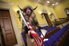 Jacob Anthony Chansley is alleged to be the man seen wearing horns and a fur hat in photographs, including this from inside the Senate chamber.