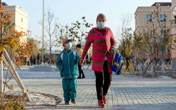 A woman and her child are on the way to their new house in Axili Town of Changji, northwest China's Xinjiang Uygur Autonomous Region, Oct. 16, 2020.