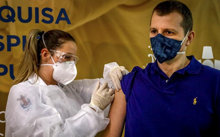 Health worker and volunteer Luciano Marini receives a COVID-19 vaccine produced by Chinese company Sinovac Biotech at the Sao Lucas Hospital, in Porto Alegre, southern Brazil on August 08, 2020.