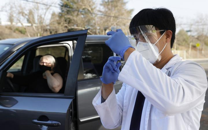 SANTA ROSA, CALIFORNIA - JANUARY 13: Safeway pharmacist Preston Young fills a syringe with Moderna COVID-19 vaccination during a drive-thru COVID-19 vaccination clinic at the Sonoma County Fairgrounds on January 13, 2021 in Santa Rosa, California.