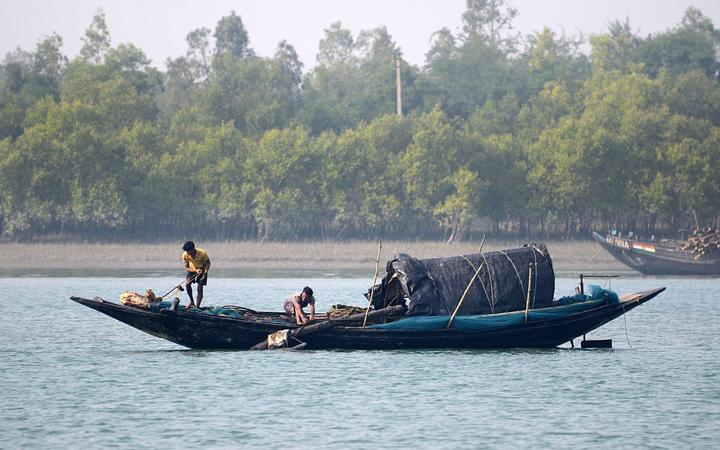 Indian Fishermen catch fishes in foggy morning on the Matla river in the Sundarban, South 24 Parganas district of West Bengal, India on Sunday , 29th December, 2019.