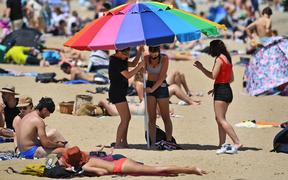 People enjoy the warm weather on Melbourne's St Kilda Beach on November 3, 2020, as Australia's Victoria state records its fourth straight day of zero transmissions of the COVID-19 coronavirus after battling a second wave of infections.