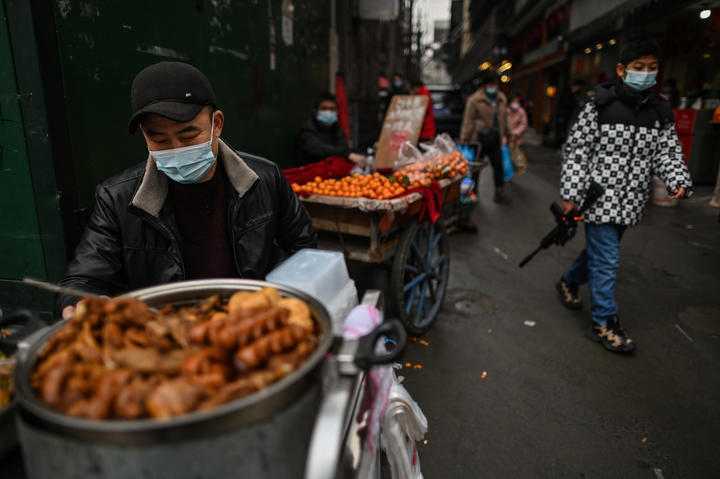 A man wearing a face mask sells food in an alley in Wuhan, China.