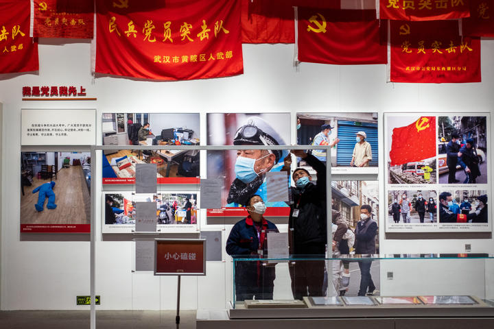 People wearing masks work at an exhibition on the fight against Covid-19, at Wuhan Parlor Convention Center.