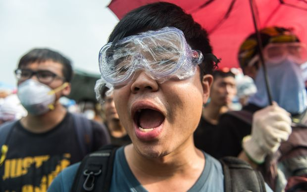 Pro-democracy protestors shout slogans at the police outside the government headquarters in Hong Kong on 3 October.