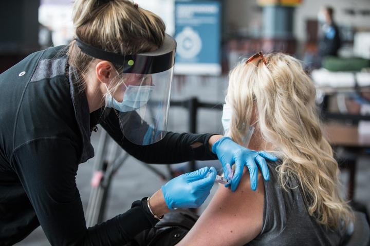 FOXBOROUGH, MA - JANUARY 15: A woman receives the COVID-19 vaccine at Gillette Stadium on January 15, 2021 in Foxborough, Massachusetts.