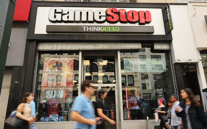 (FILES) In this file photo taken on September 15, 2019 people pass a GameStop store in lower Manhattan in New York City. G