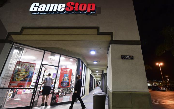 People enter a GameStop store in Alhambra, California on January 27, 2021. - An epic battle is unfolding on Wall Street, with a cast of characters clashing over the fate of GameStop, a struggling chain of video game retail stores.