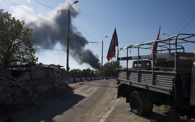 A pro-Russian separatist checkpoint in Donetsk as smoke rises from the airport area in the background.