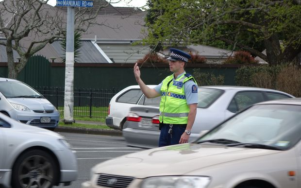 A police officer directs traffic at the intersection of Manukau and Greenlane Roads in Epsom.