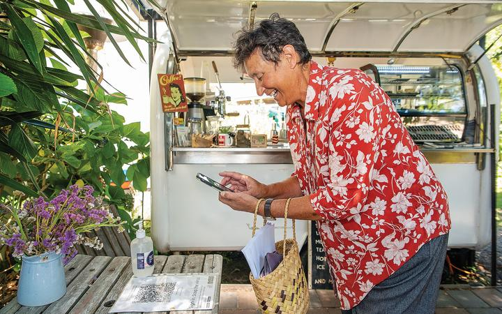 Opotiki's mayor Lyn Riesterer scans in at Kafe Friends coffee cart in the Opotiki CBD and would like the rest of the community to do the same.