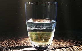 A glass of water showing a farm