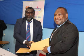 PNG's prime minister James Marape (right) shakes hands with Ishmael Toroama, the president of the autonomous region of Bougainville, 5 February 2021.