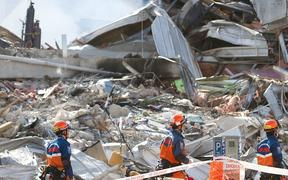 Japanese rescuers walk past the smoking ruins of the CTV building where 4in Christchurch on February 24, 2011, two days after a deadly earthquake rocked New Zealand's second city