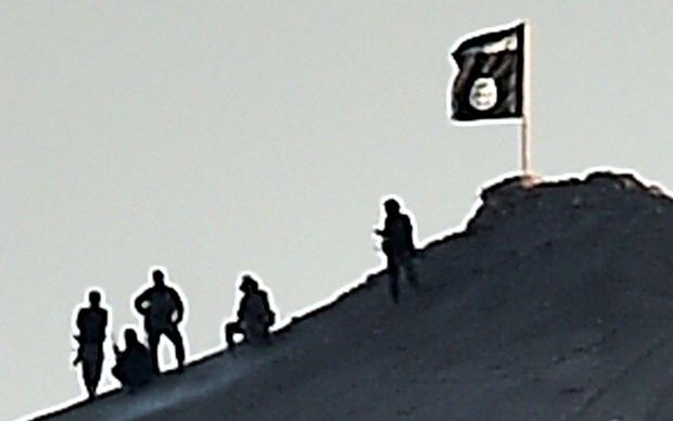 An Islamic State flag on a hill by Kobane - another was on a building on the eastern side of the Syrian border  town.