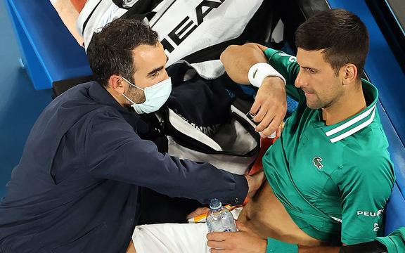 Serbia's Novak Djokovic gets medical treatment while playing against Taylor Fritz of the US during their men's singles match on day five of the Australian Open tennis tournament in Melbourne on February 12, 2021.