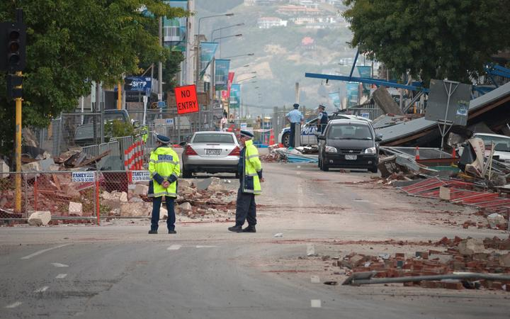 Police stand by amid fallen debris in a cordoned-off street in the aftermath of the Christchurch earthquake.