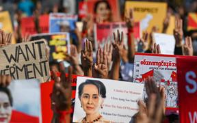Protesters hold up the three finger salute with signs calling for the release of detained Myanmar civilian leader Aung San Suu Kyi during a demonstration against the military coup in Yangon on 16 February, 2021.