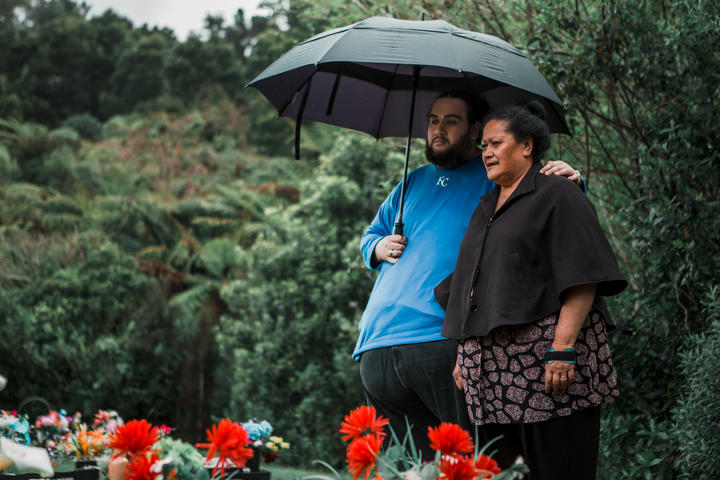 Albert and Lina Fairbrother stand under an umbrella at Taita Cemetery