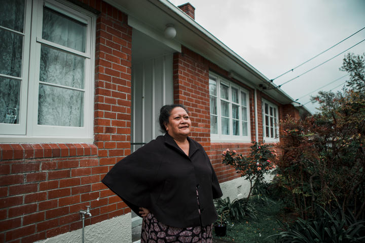 Lina stands outside her home in Naenae