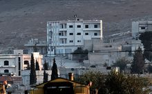 An Islamic State flag flutters on the roof of a building inside the Syrian town of Kobane. Another larger flag was planted on a hill.